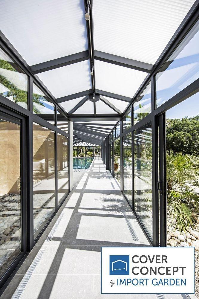 Un abri de piscine véranda avec couloir d'accès par Cover Concept