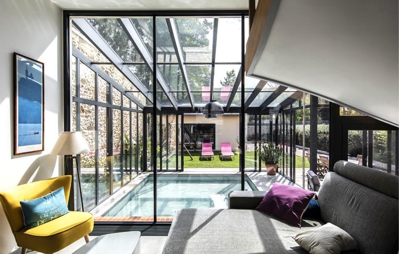 Piscine intérieure sous une véranda en extension d'habitation