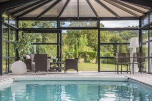 Détente au bord de la piscine dans la véranda contemporaine avec toiture en polycarbonate bronze
