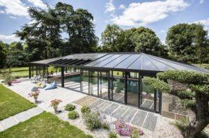 Vue extérieure de l'abri piscine avec toiture en polycarbonate bronze