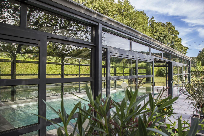 Nature omniprésente depuis la piscine grâce au châssis en aluminium et double vitrage de la véranda
