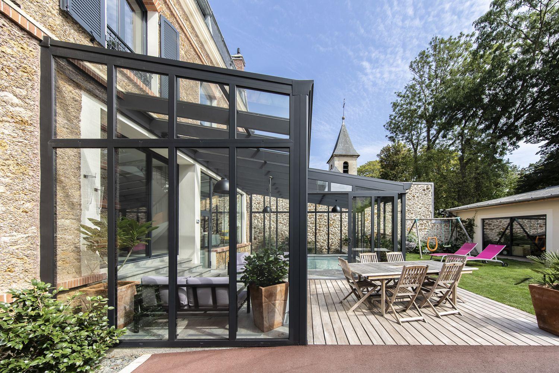 Véranda pour piscine design accessible depuis le salon ...