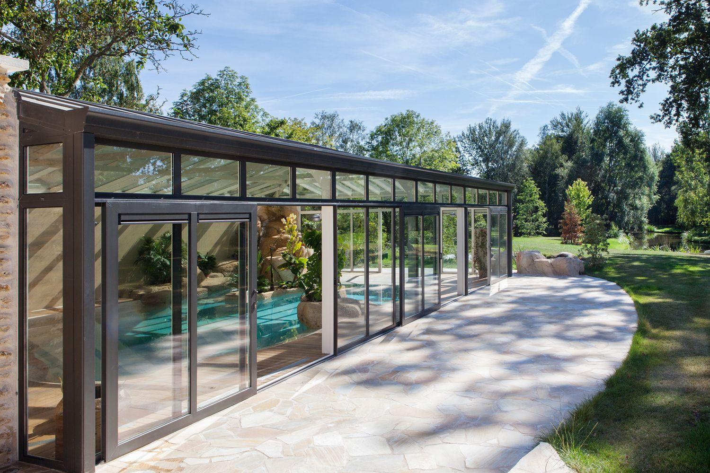 Intégration parfaite de la véranda pour piscine adossée à la maison dans un cadre verdoyant