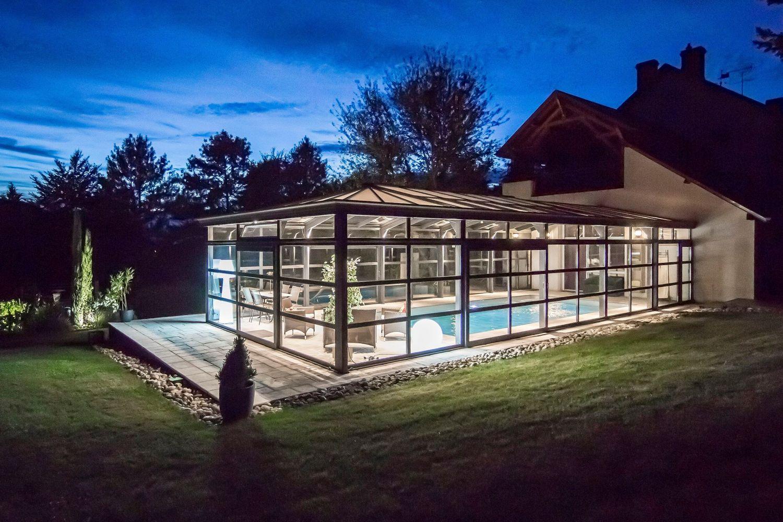 Véranda Cover Concept Virginia couvrant une piscine éclairée de nuit
