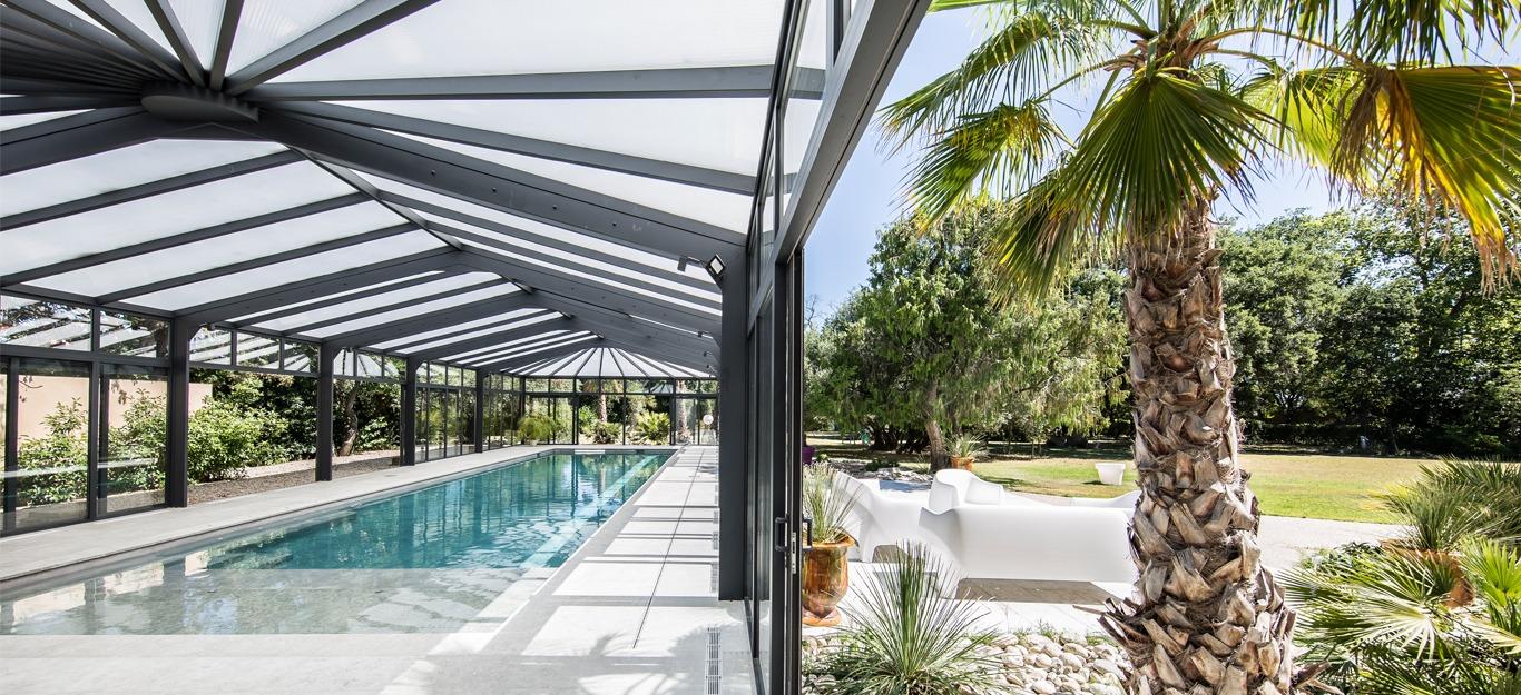 Véranda pour piscine donnant sur l'extérieur avec baies ouvrantes