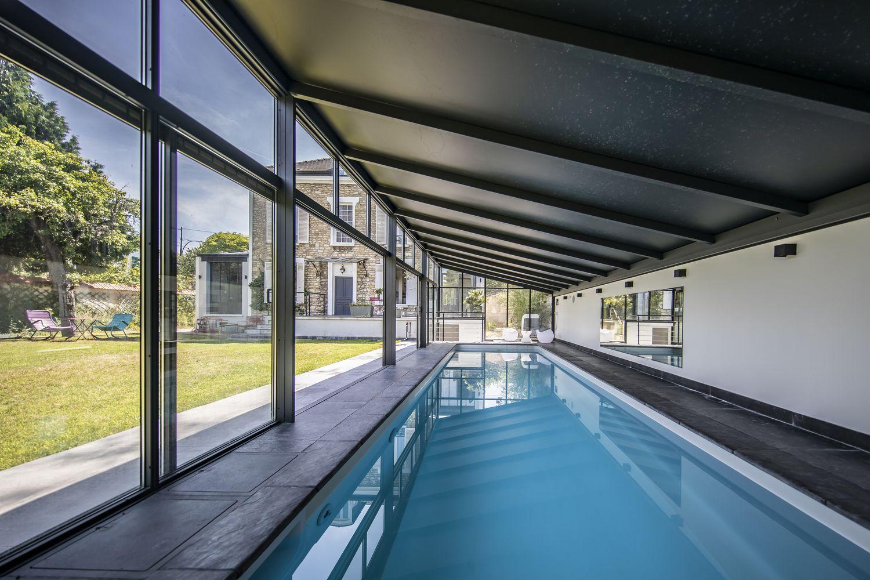 Grandes baies vitrées pour profiter du jardin en nageant dans la piscine.