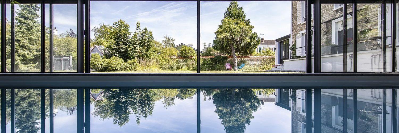 Piscine couverte par une véranda largement ouverte sur le jardin