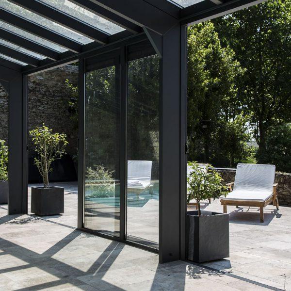 Porte coulissante ouverte pour profiter un maximum de l'extérieure depuis la véranda pour piscine