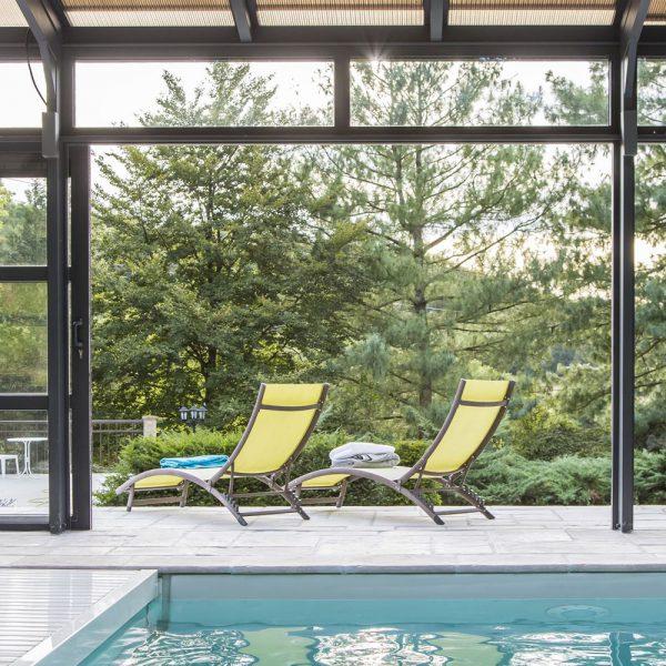 Grande ouverture sur la nature pour se relaxer grâce aux baies coulissantes de l'abri piscine