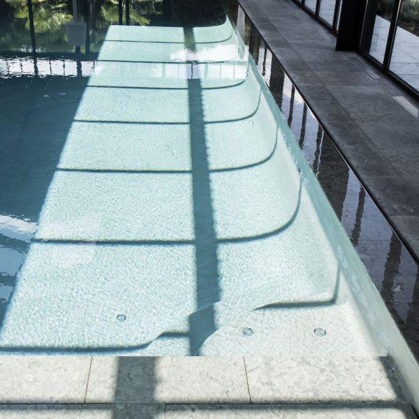 Reflet du soleil dans l'eau grâce aux doubles vitrages de la toiture