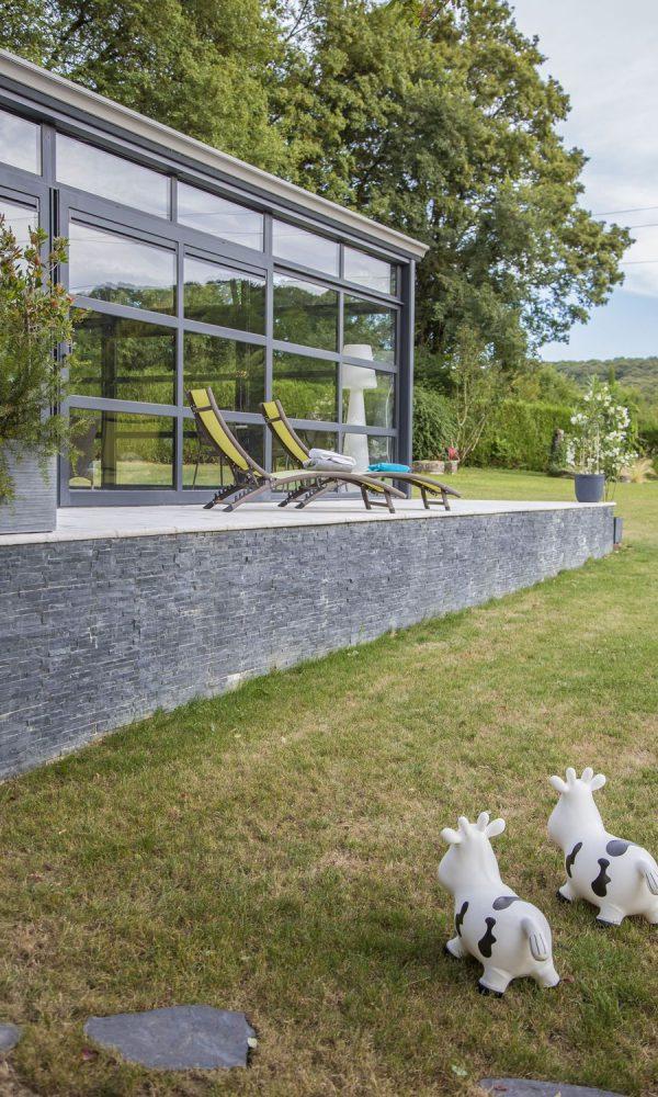 Véranda pour piscine design au cœur d'un jardin verdoyant