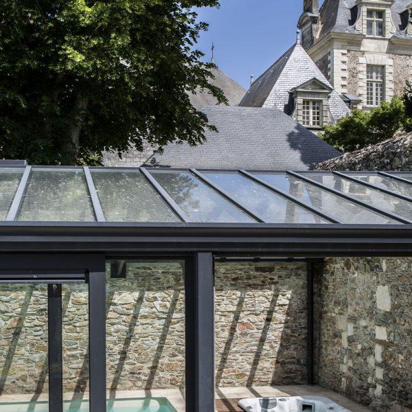 Véranda pour piscine parfaitement intégrée à un bâtiment de France