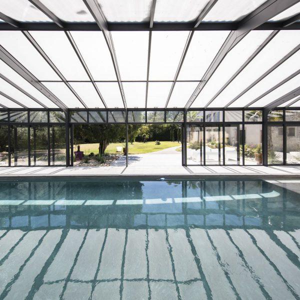 Abri piscine avec baies coulissantes et toitures en polycarbonate