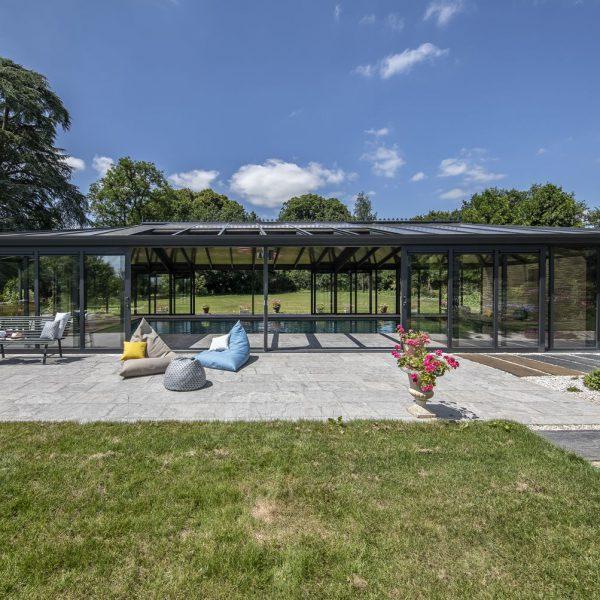 Large véranda pour piscine avec grande baies coulissantes ouvertes