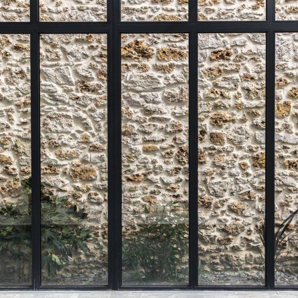 Mariage parfait entre les châssis en aluminium de la véranda et le mur en pierre rustique