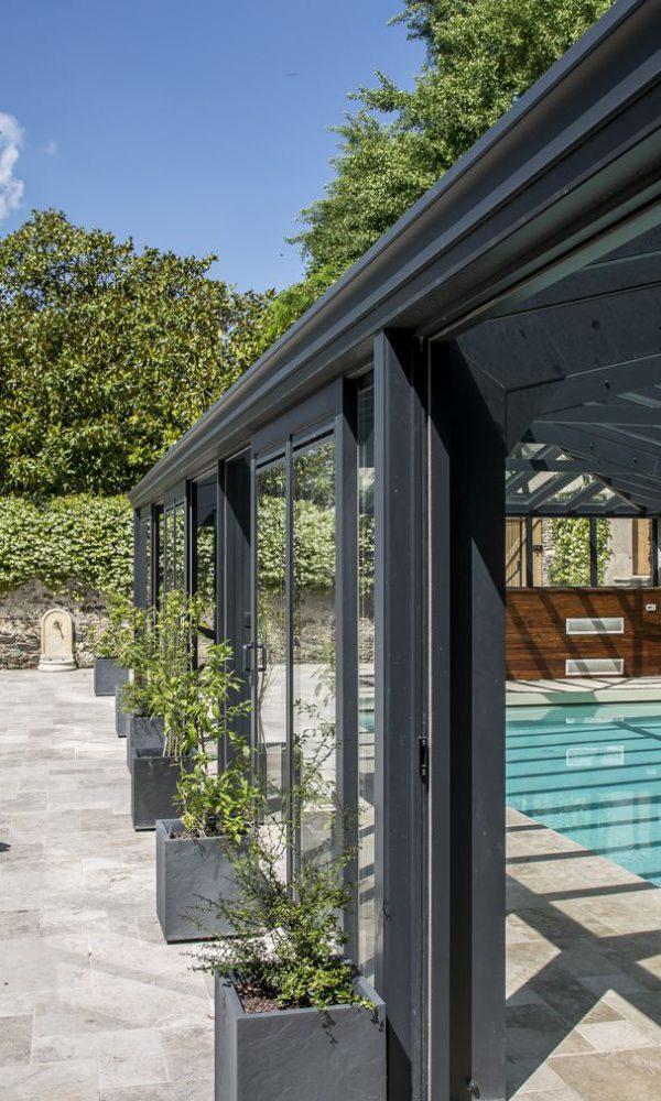 Design sobre et élégant d'abri piscine avec baies coulissantes
