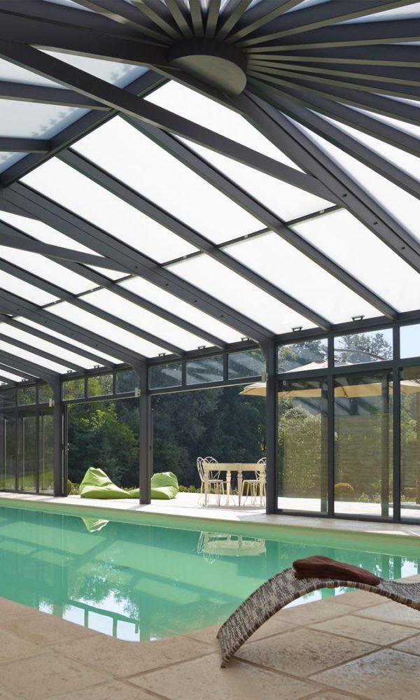 Détente au bord de la piscine illuminée par les reflets du soleil sur la toiture en polycarbonate