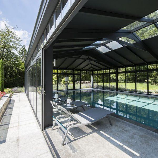 Élégance totale de la véranda grâce à sa toiture mixte en double vitrage et panneaux sandwich noir