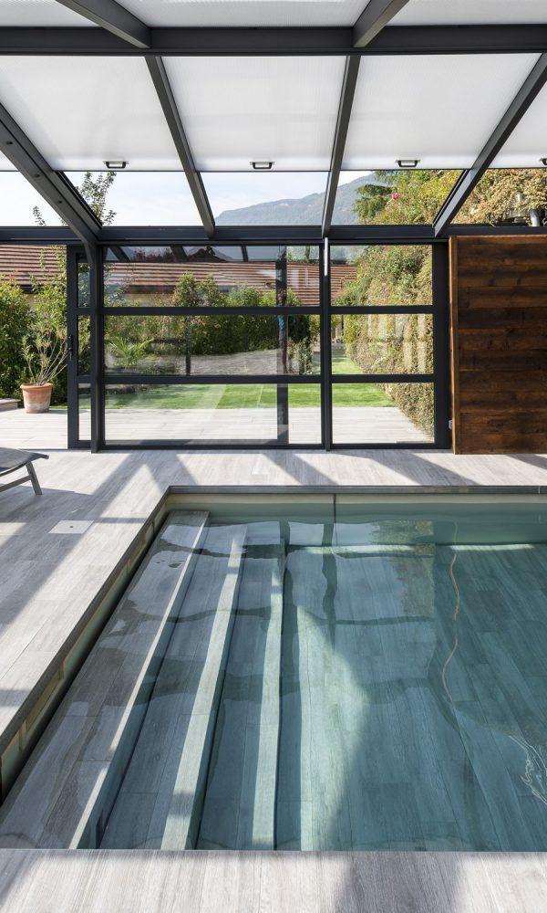 Ouverture sur la nature avec les porte coulissante vitrée de la véranda pour piscine