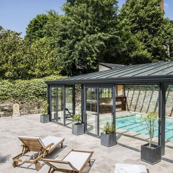 Coin détente au soleil donnant sur les portes coulissante de la véranda pour piscine
