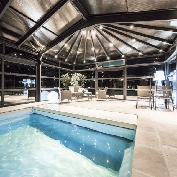 Coin détente au bord de la piscine illuminé par l'abri piscine