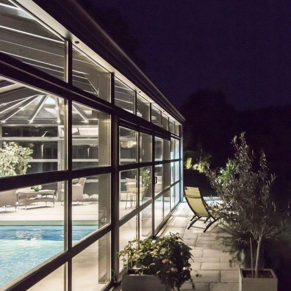 Terrasse extérieur éclairée par les lumières de la véranda pour piscines
