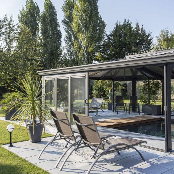 Terrasse extérieure ensoleillée avec accès à la piscine par les baies coulissantes de la véranda