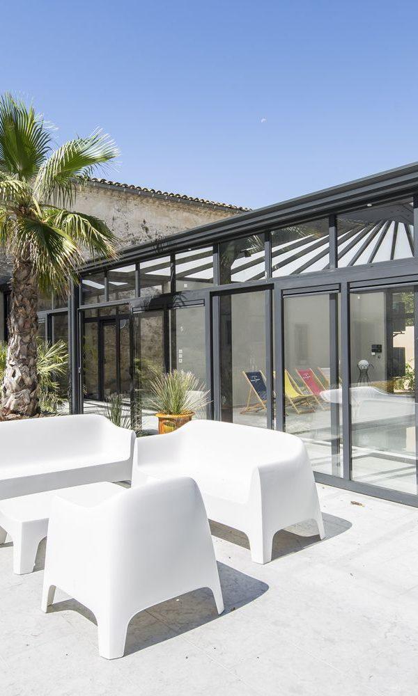Terrasse exotique ensoleillée au bord de l'abri piscine