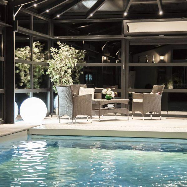 Salon de détente au bord de la piscine illuminé par les spots de la véranda pour piscine