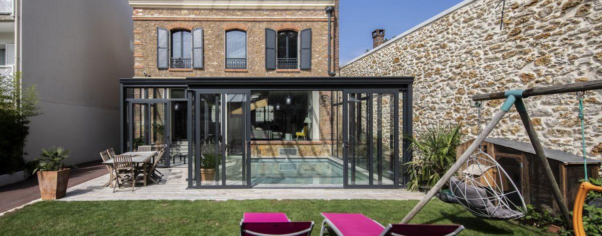 Détente au jardin avec vue sur la piscine grâce aux portes coulissantes de la véranda