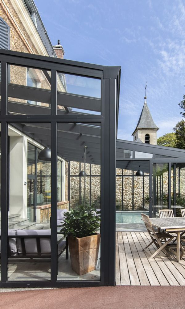 Intégration parfaite de la véranda pour piscine dans un jardin de ville