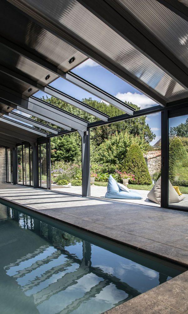 Abri pour piscine en aluminium avec toits ouvrants et baies coulissantes