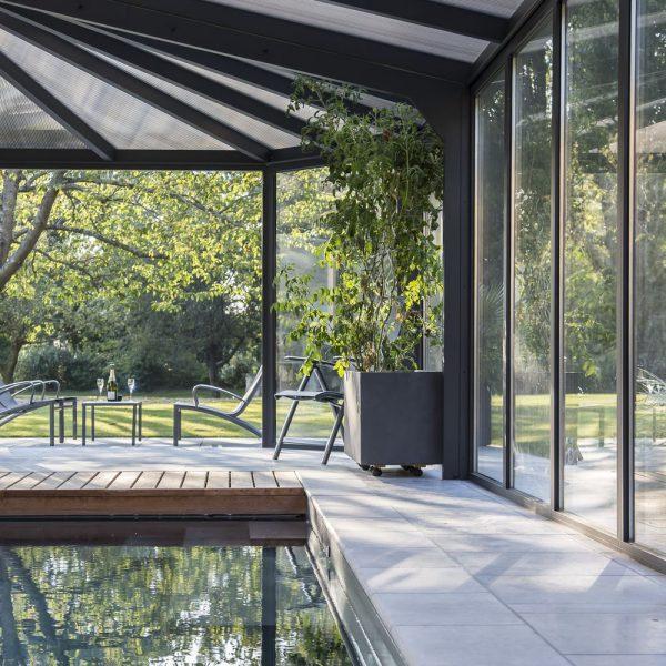 Véranda pour piscine sur mesure avec toiture travaillée en polycarbonate bronze